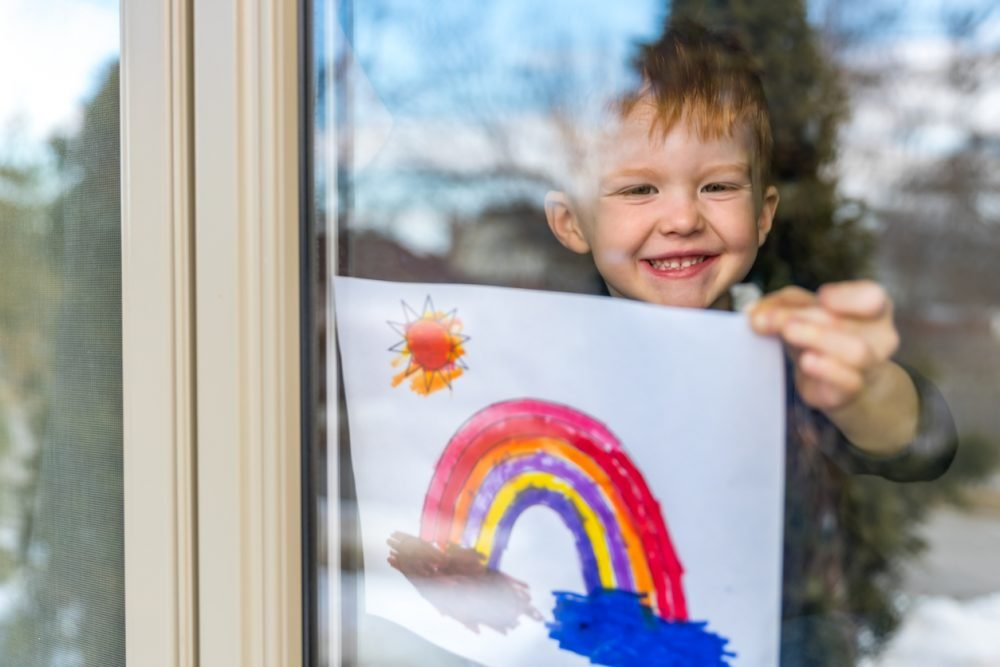 Young Boy sticking his rainbow drawing on home window during the Covid-19 crisis
