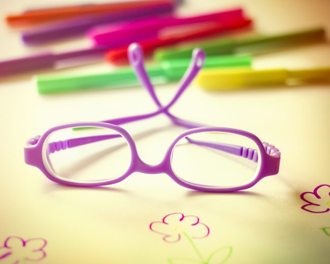 Kid's eyeglasses on desk with color markers