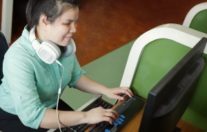 A young visually-impaired woman on an adapted computer, using a screen reader