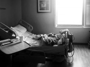 Black and white photo of an unmade, empty hospital bed