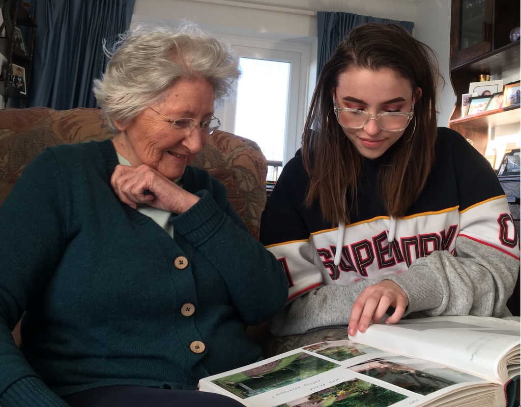 Mum and granddaughter looking at a photo album and smiling.