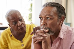 depression: older woman comforting a man