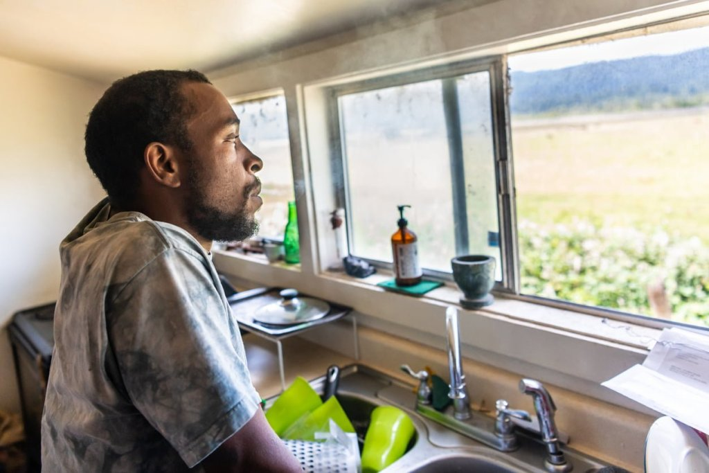 Serious Afr-Caribbean man looking out of the kitchen window